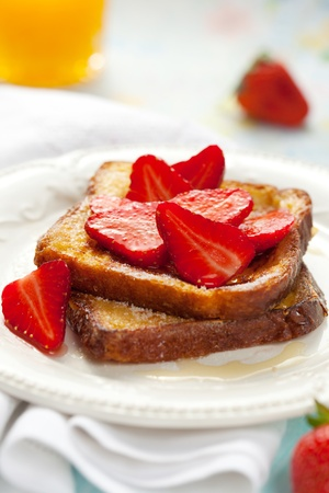 traditionally french: French toast with strawberries, maple syrup and  sugar Stock Photo