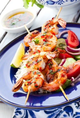 spicy: Prawn skewers with rice and vegetable salad Stock Photo