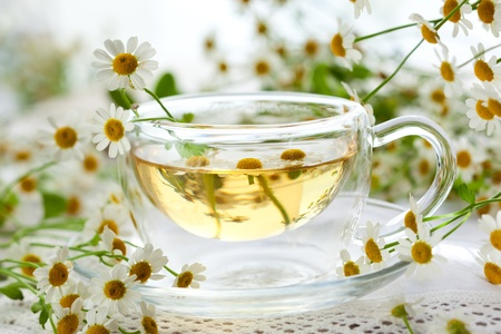 Chamomile tea in glass cup with flowers photo