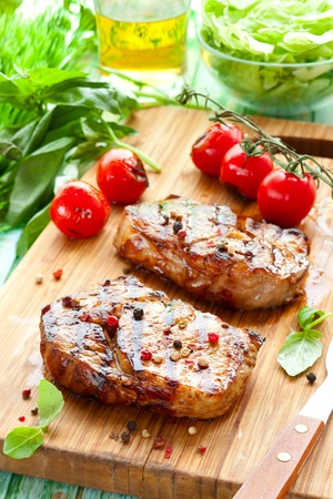 Grilled veal loin steak on cutting board photo