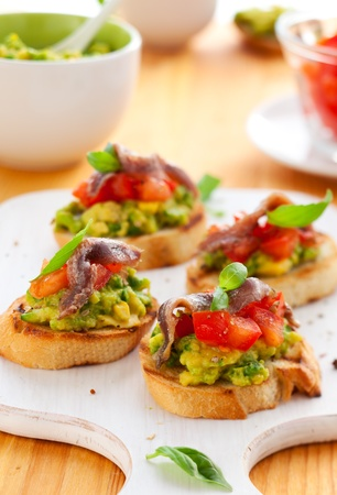anchovy fish: avocado,tomato and anchovy crostini on cutting board Stock Photo