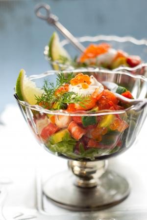 Shrimp, avocado, salmon and caviar cocktail  salad in a glass photo