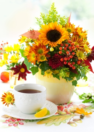 fall still life with cup of tea and autumnal flowers photo