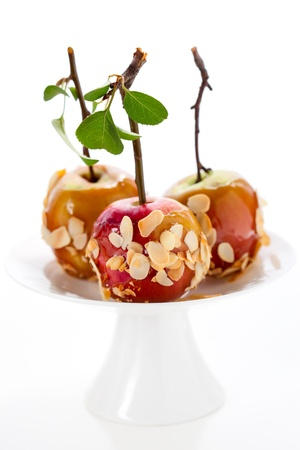 Caramel apples with nut coating on a wooden stick photo
