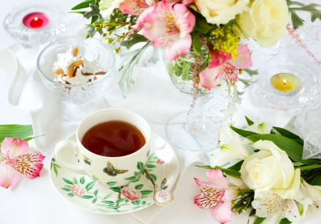 light breakfast: beautiful flowers in vase , cup of tea and biscuits