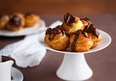 Profiteroles with cream and chocolate sauce photo