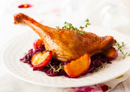cooked meat: Roasted duck leg with red cabbage and apples for Christmas