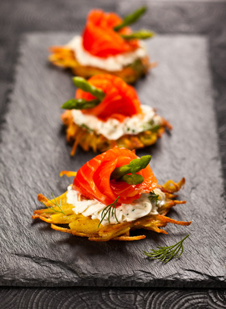 Potato pancakes topped with smoked salmon,asparagus and sour cream for holiday photo