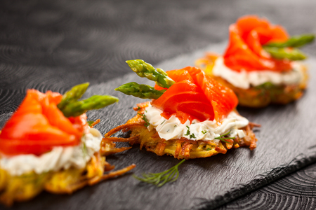 food buffet: Potato pancakes topped with smoked salmon,asparagus and sour cream for holiday Stock Photo