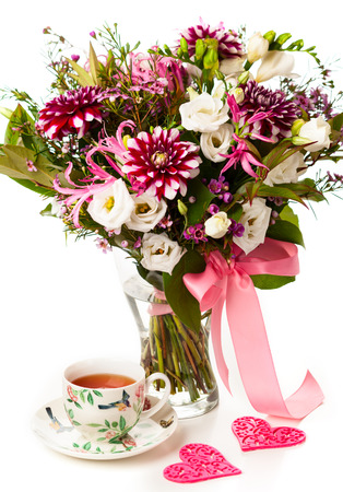 Beautiful  bouquet of flowers  and cup of tea photo