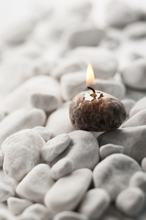 Burning candle and white stones