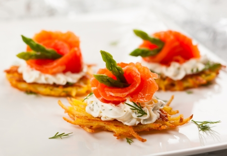 holiday catering: Potato pancakes topped with smoked salmon,asparagus and sour cream for holiday Stock Photo