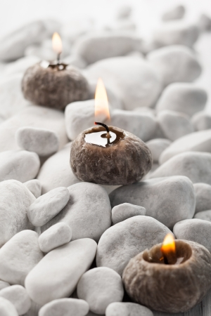 Burning candle and white stones photo