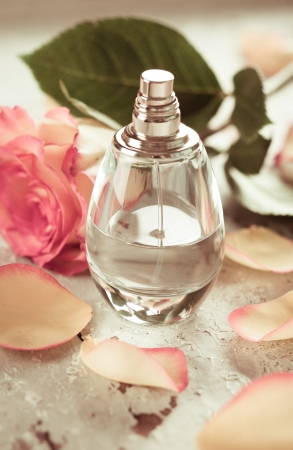 scented: perfume bottle and rose on the old desk  in vintage style