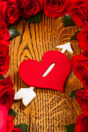 heart pierced by  cupid arrow and red roses on the wooden background photo