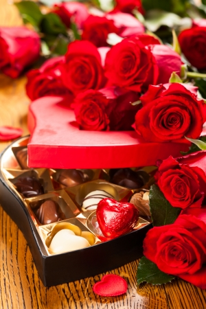 Heart shaped box of chocolate truffles with red roses photo