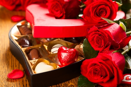 valentine s day: Heart shaped box of chocolate truffles with red roses Stock Photo