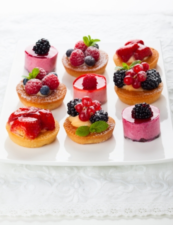 Assorted  fruit tartlets and pieces of cakes for holiday photo