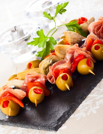 Antipasti skewers with olives,red pepper,artichoke hearts and salami photo