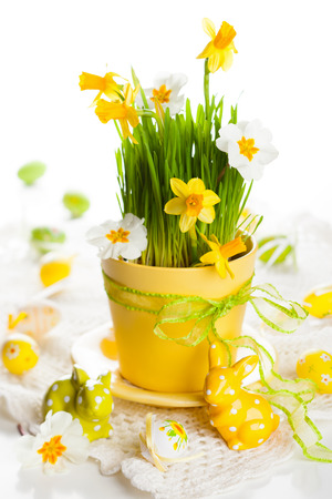 Spring flowers and green grass in a pot and Easter  eggs and rabbits photo