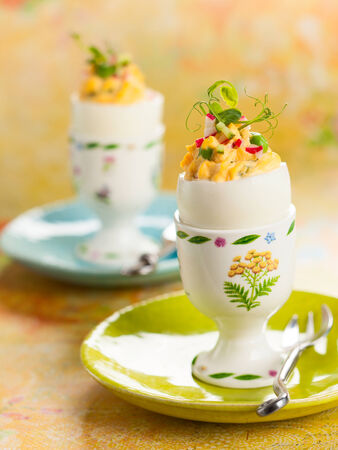 Stuffed eggs filled with cucumber,radish and green pea for Easter photo