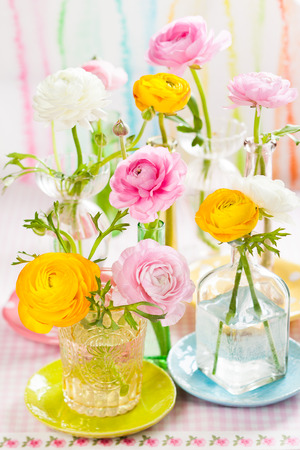 Beautiful colorful ranunculus in  glass bottles photo
