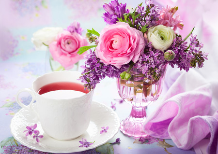 Beautiful spring flowers in vase and cup of tea photo