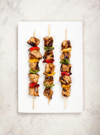 brochetas de frutas: Carne y vegetales kebabs a la parrilla en la placa blanca