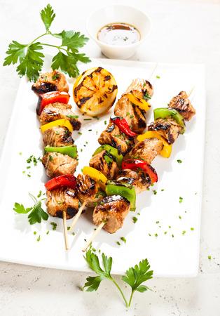 Carne y vegetales kebabs a la parrilla en la placa blanca