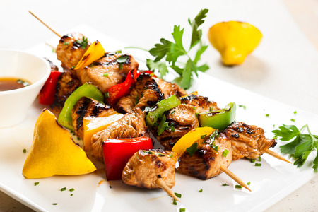 marinade: Grilled meat and vegetable kebabs on the white plate Stock Photo