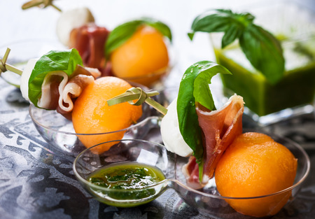 Appetizer with melon,mozzarella and prosciutto on skewers photo