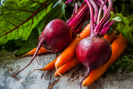 Fresh organic carrots and beetroot  on old wooden board photo