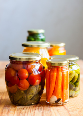 Vegetable preserves on wooden table photo