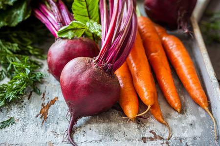 Frische Bio-Karotten und Rote Beete auf alten Holzbrett