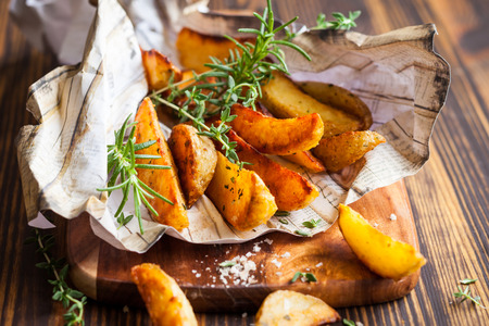 Roasted potato wedges with herbs and salt Imagens