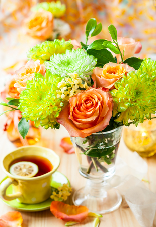 Autumnal table setting with  bunch of autumn flowers and cup of tea photo