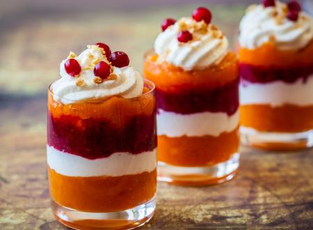 Layered pumpkin and cranberry dessert with cream