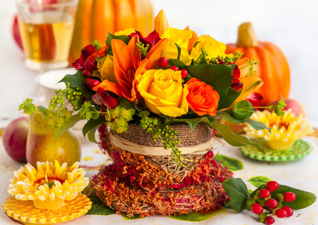 Festive table setting with basket of autumn flowers and pumpkin photo