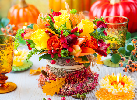 Festive table setting with basket of autumn flowers,candle and pumpkin. Selective focus.