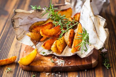 papas fritas: Porciones de patatas asadas con hierbas y sal