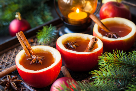 Apple cider with cinnamon sticks and anise star in apple cups photo