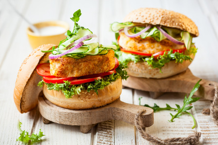 crab meat: Fish and crab burgers with fresh vegetables on wooden serving boards