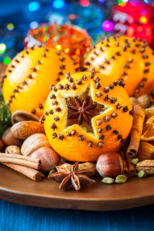 Oranges pierced with cloves,Christmas spices and nuts photo