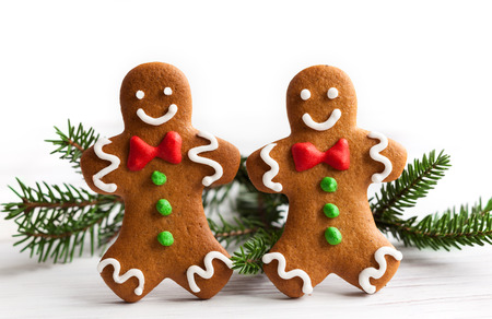 Smiling gingerbread men on white wooden background photo