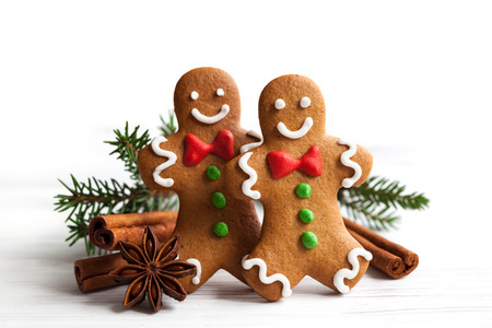 Smiling gingerbread men on white wooden background Archivio Fotografico