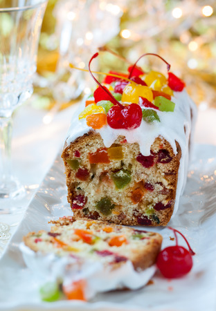 Christmas fruitcake with sugar icing and candied fruits photo