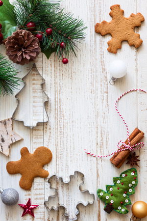rustic food: Christmas background with gingerbread,cookies cutters,fir  branches and spices on the old wooden board