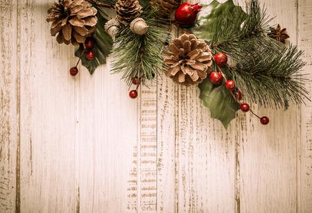 Kerst achtergrond met dennentakken, dennenappels en bessen op de oude houten bord