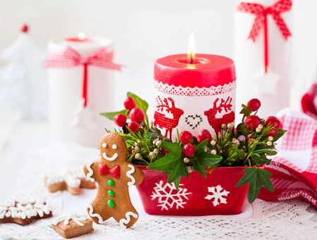 flower arrangements: Christmas table decorated with candle,flowers and gingerbreads Stock Photo