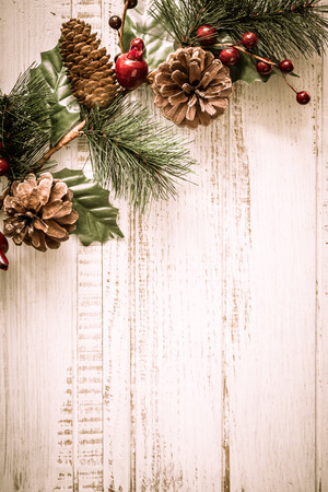 Christmas background with fir branches,pinecones and berries on the old wooden board in vintage style photo